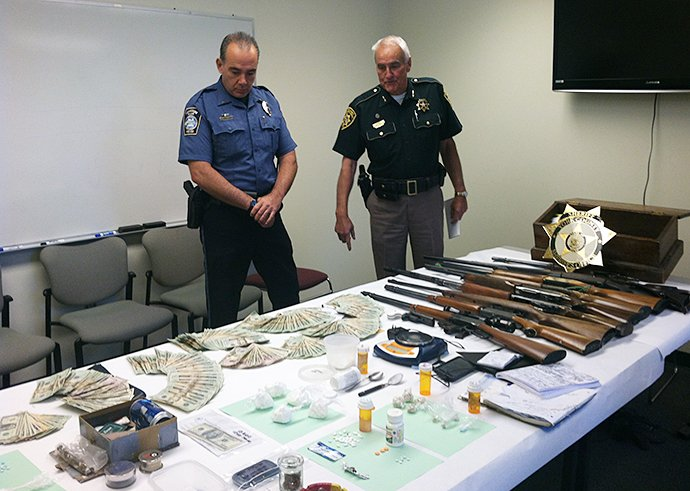 Kennebunk Lt. Daniel Jones, left, and York County Sheriff Maurice Ouellette display drugs and weapons seized during a search at a suspected drug house in Kennebunk. Photo provided by York County Sheriff's Office.