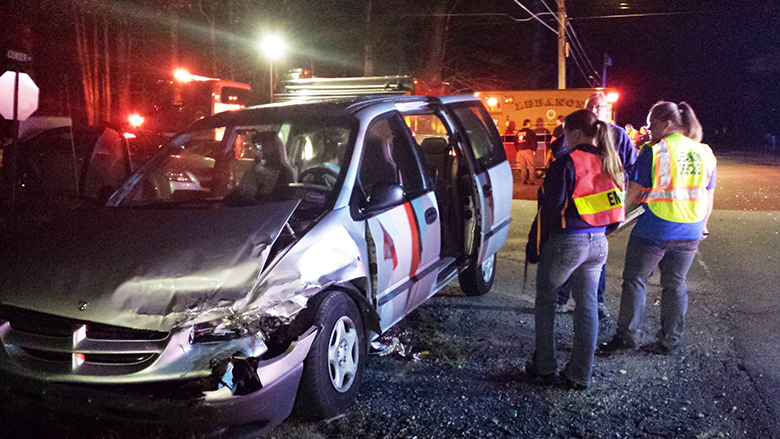 Emergency personnel examine one of the minivans involved in a collision on Center Road at the intersection of Lower Cross Road in Lebanon Monday night.