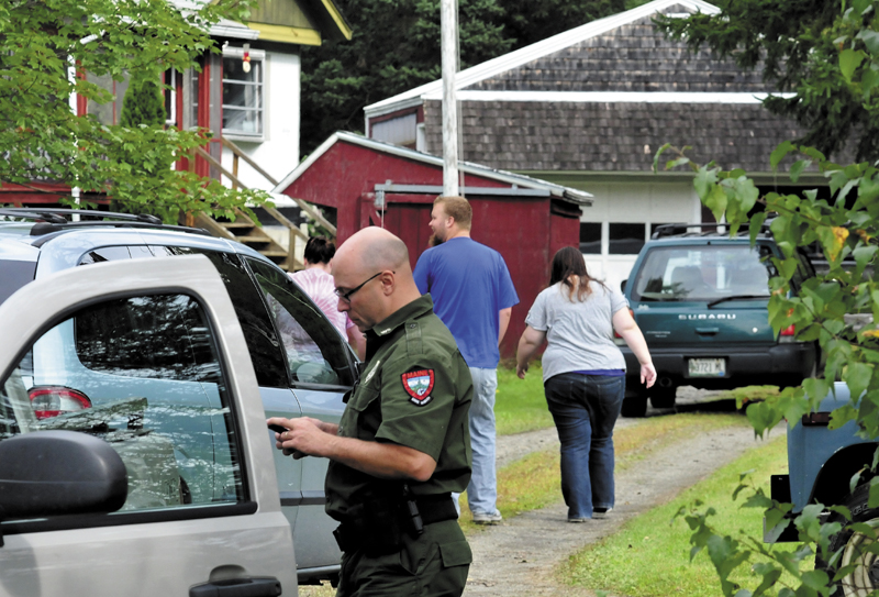 Game Warden Steven Couture prepares to search for Arthur Wakeman behind his residence in Benton on Thursday, as family members arrive at the home. Wakeman was reported missing Wednesday evening.