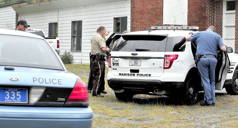 Somerset County deputy sheriffs, center, and a Maine State Police trooper, right, speak to James L. Mayo, inside a Madison Police Department cruiser, who was arrested near the Cornville Regional Charter School on Monday.