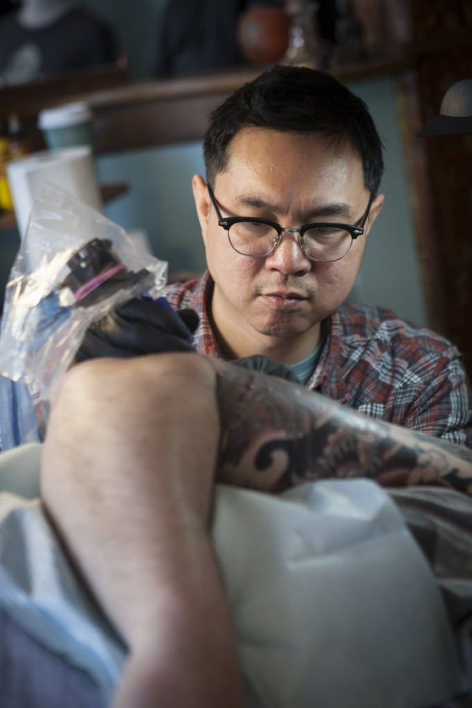 "Phuc Tran of Tsunami Tattoo, in Portland, is part of the new wave of tattoo practitioners, college-educated businessmen with detailed professional portfolios. Tran considers himself a ""tattoist"" or ""tattoer."""