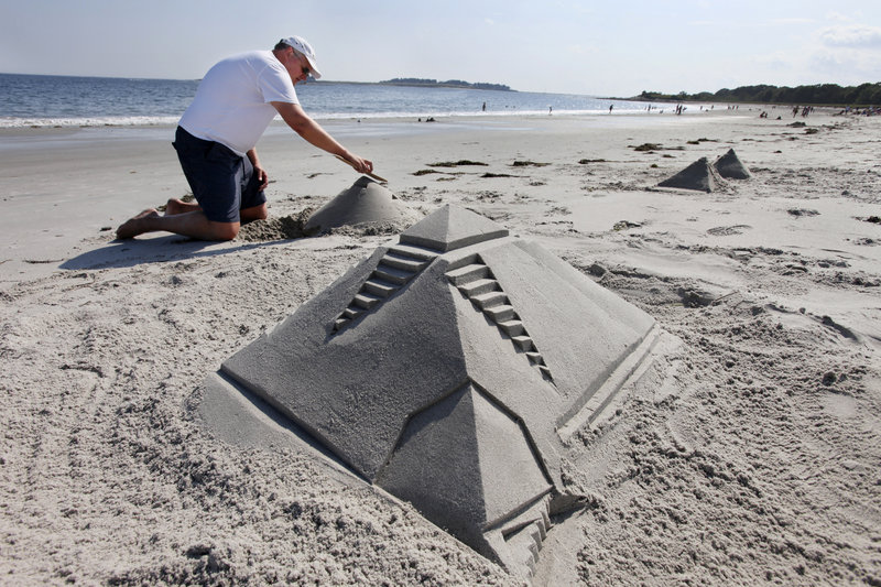 Scott Smyth of Falmouth works on sand sculptures Friday at Crescent Beach in Cape Elizabeth. Data show this summer has been pretty typical.