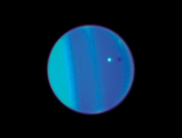 This Hubble Telescope image shows Uranus with its moon Ariel, a small white sphere. The discovery of Trojan 2011 QF99 was reported in the journal Science.