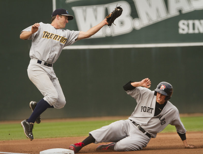 Garin Cecchini slides safely into third base, advancing from second on a wild pitch during the third inning of a 9-4 loss to the Trenton Thunder at Hadlock Field on Sunday. The Sea Dogs wore retro-style 1926 uniforms.