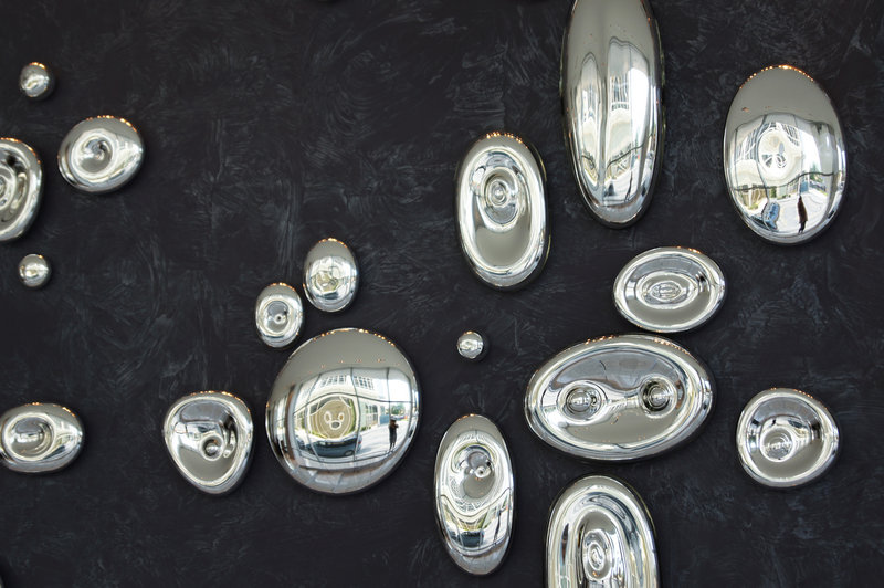 Pebble shapes made of mercury glass, from Bueno Glass, represent sound waves or electrons.