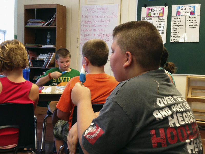 Fourth-graders eat popsicles to stay cool as their teacher reads to them on a hot day in a Monticello, Ill., classroom last week.