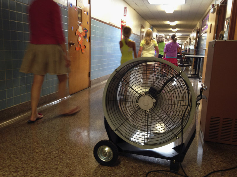 A teacher and students at Washington Elementary School in Monticello, Ill., walk past a large fan last week. The school, built in 1894, has air conditioning in only a few spots and has been sending students home early due to a heat wave.