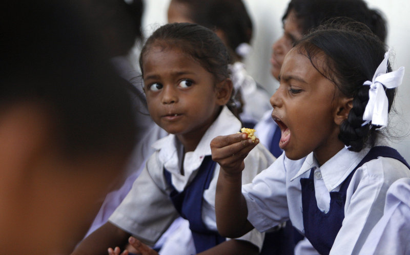 An Indian girl eats a free midday meal at a government school last month. The government will give free food to kids under 6 years old as part of a recently authorized program.