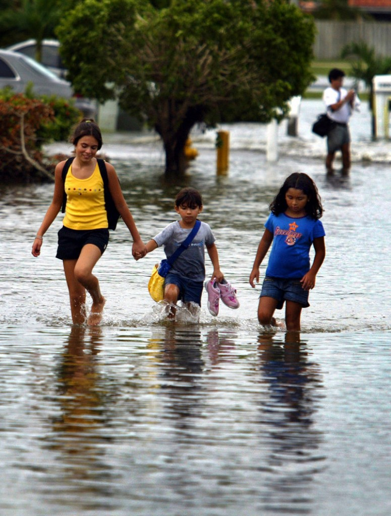 Two school-age children are led down a flooded street in Dade County, Fla., after Katrina brushed by in 2005. Many school districts still lack emergency plans for schools that would help authorities safeguard students.