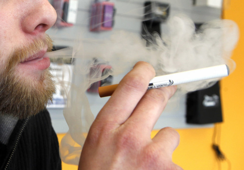 A sales associate demonstrates use of an electronic cigarette and the resulting smoke-like vapor in Colorado. The U.S. government does not regulate e-cigarettes.