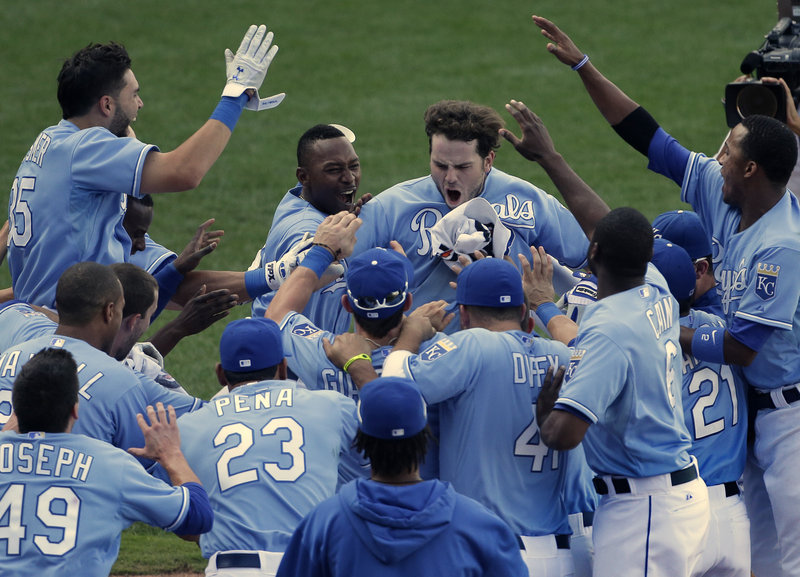 Mike Moustakas, center, celebrates with his teammates after hitting a solo homer in the 13th inning to lift the host Kansas City Royals to a 7-6 victory over the Seattle Mariners.