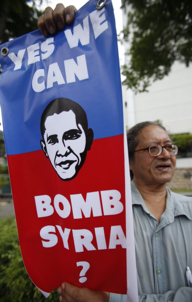 Protesters have been gathering around the world during the past week to speak out against a U.S. campaign against Syria. Here, a demonstrator displays a placard outside the U.S. embassy in Kuala Lumpur, Malaysia, on Friday.