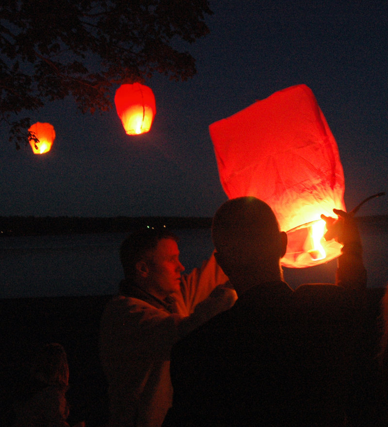 Co-workers, friends and family of Lynn Arsenault, who was slain in Belfast on Aug. 28, launch candlelit balloons over Belfast Harbor on Friday evening.