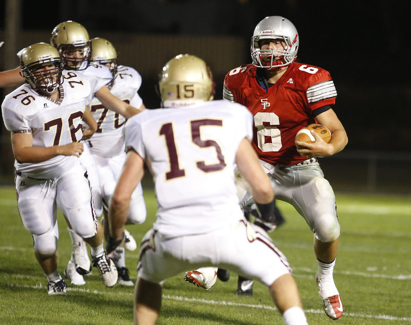 Duncan Preston, who ran for 137 yards and threw four touchdown passes Friday night for South Portland, weaves his way through the Thornton Academy defense for a first down in the second half. South Portland defeated the defending Class A champion, 26-13.