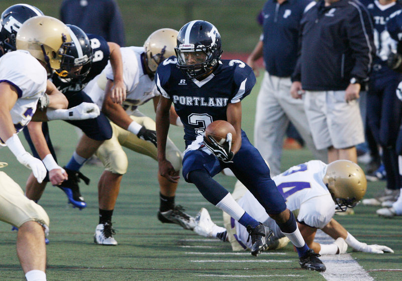 Jordan Talbot of Portland gains yards and looks for more Friday night during the opener Friday night against Cheverus at Fitzpatrick Stadium. Cheverus won, 35-25.