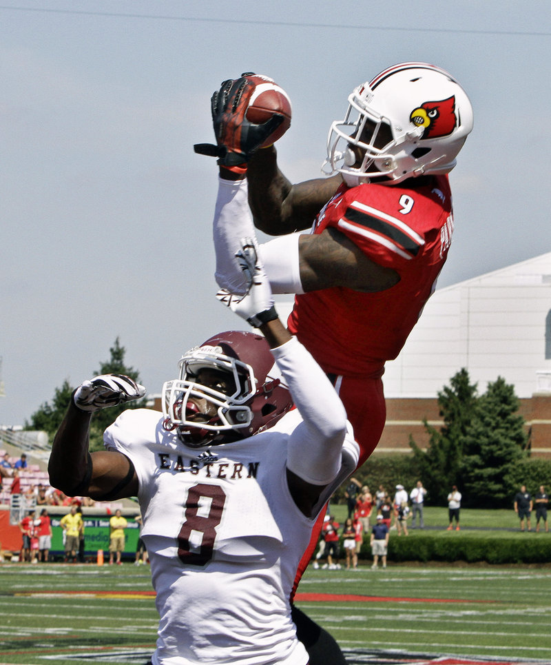 Louisville receiver DeVante Parker hauls in a 19-yard reception despite the efforts of Eastern Kentucky defender Johnny Joseph in Saturday's 44-7 win at Louisville, Ky.