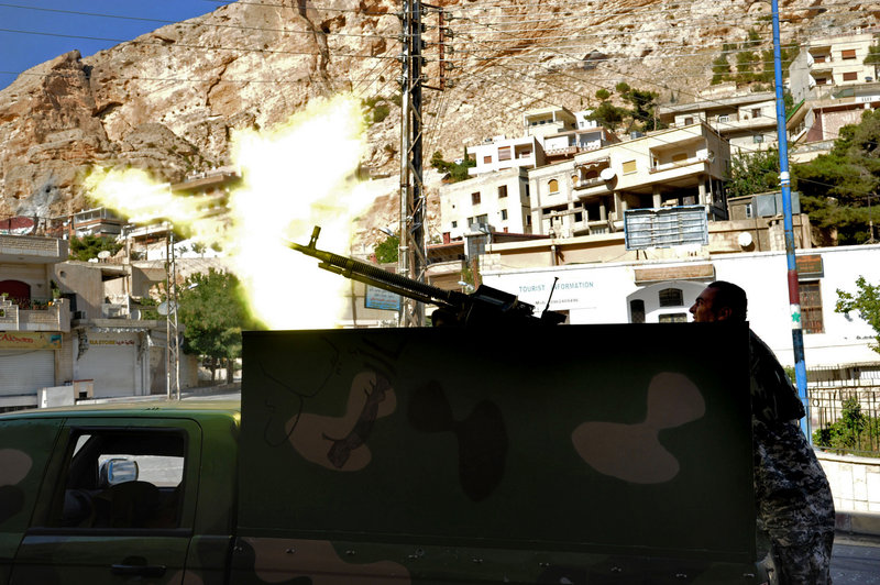 In a photo released by the Syrian official news agency SANA, a Syrian government soldier fires a heavy machine gun Saturday during clashes with rebels northeast of the capital, Damascus. While it's easy to see how U.S. military intervention in Syria could go wrong, it's difficult to image what success would look like.