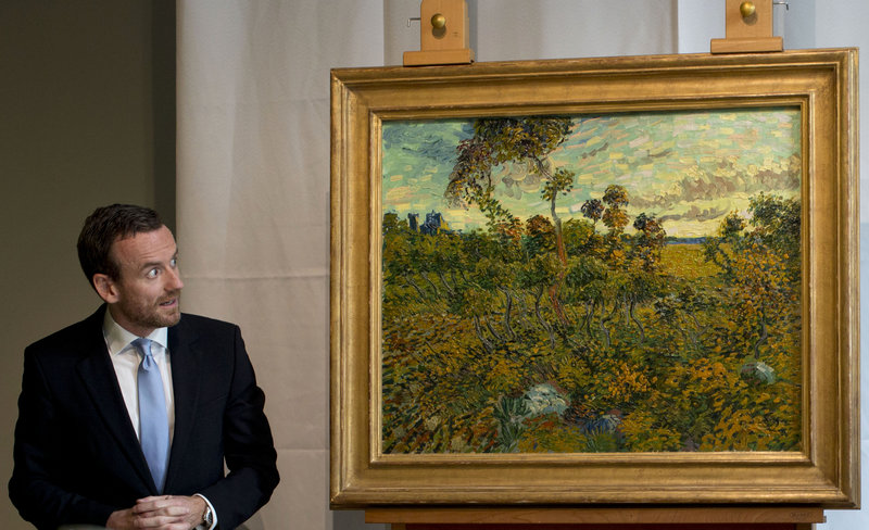 "Van Gogh Museum director Axel Rueger looks at ""Sunset at Montmajour"" after unveiling the painting by Dutch painter Vincent van Gogh during a news conference at the museum in Amsterdam on Monday. It's the first van Gogh discovery since 1928."