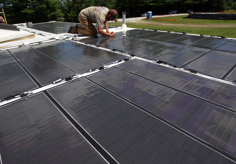 In this July 30, 2013 photo, student Brad Paisker checks photo-voltaic panels on the roof of the Norwich University solar-powered home in Northfield, Vt. Vermont's Norwich University and Middlebury College are sending their student-designed solar homes to the U.S. Department of Energy Solar Decathlon in California. There are 20 teams from across the globe competing for bragging rights about the best way to use the sun to power houses.(AP Photo/Toby Talbot)