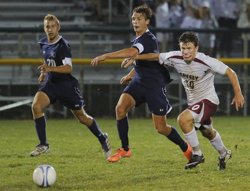 Greely's Matthew Crowley (10) tries to hold back Yarmouth's David Murphy (4) and Chandler Smith (20) while going for the ball late in the second half Tuesday.
