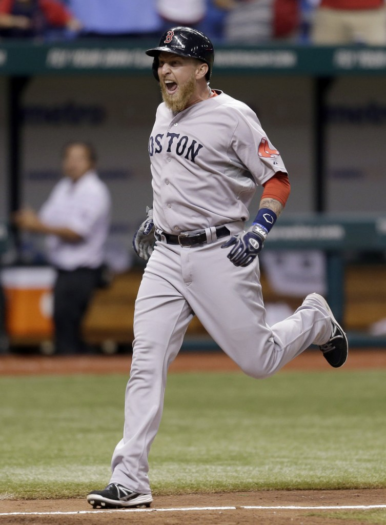 Mike Carp reacts Wednesday night as he heads for the plate after his 10th-inning grand slam helped lift the Red Sox over the Rays, 7-3.