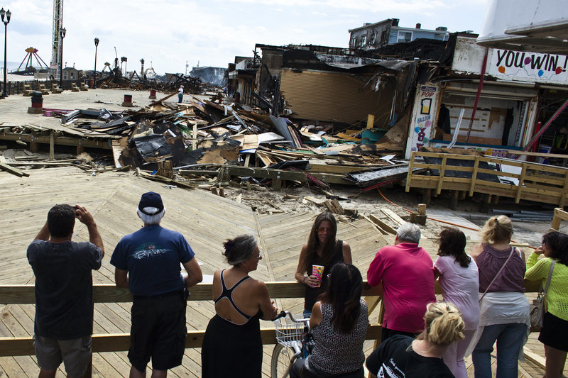People look at the remnants of the boardwalk Friday after a massive fire in Seaside Park, N.J.