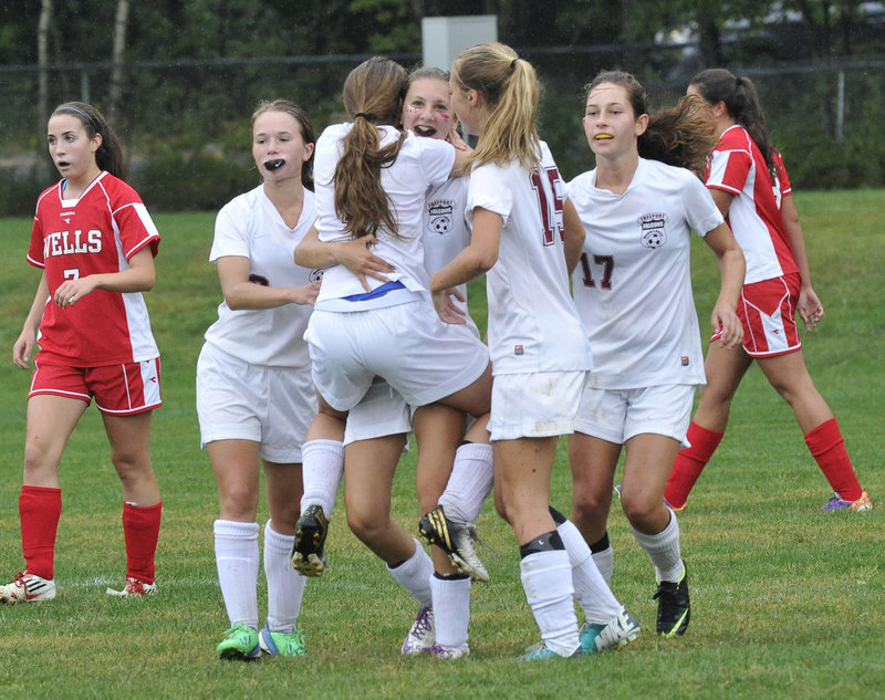 Brooke Heathco, center, gets a hug from Freeport teammate Alyssa Richardson after scoring the first goal in the Falcons' 2-1 win Friday over Wells.
