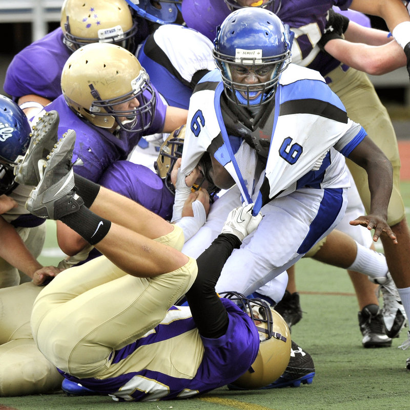 Quintarian Brown of Lewiston is pulled down by Justin Johnson, bottom, with help from Cody O'Brien, left and the rest of the Cheverus defense.