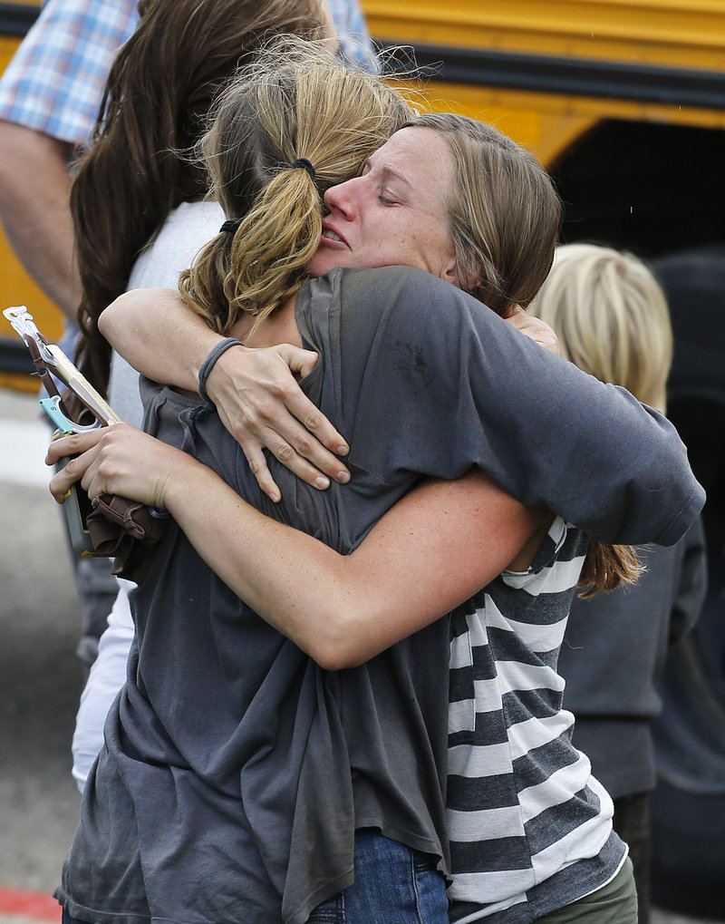 Evacuees hug at a school in Niwot, Colo., on Saturday, as the rescue of hundreds stranded by epic mountain flooding was accelerating.