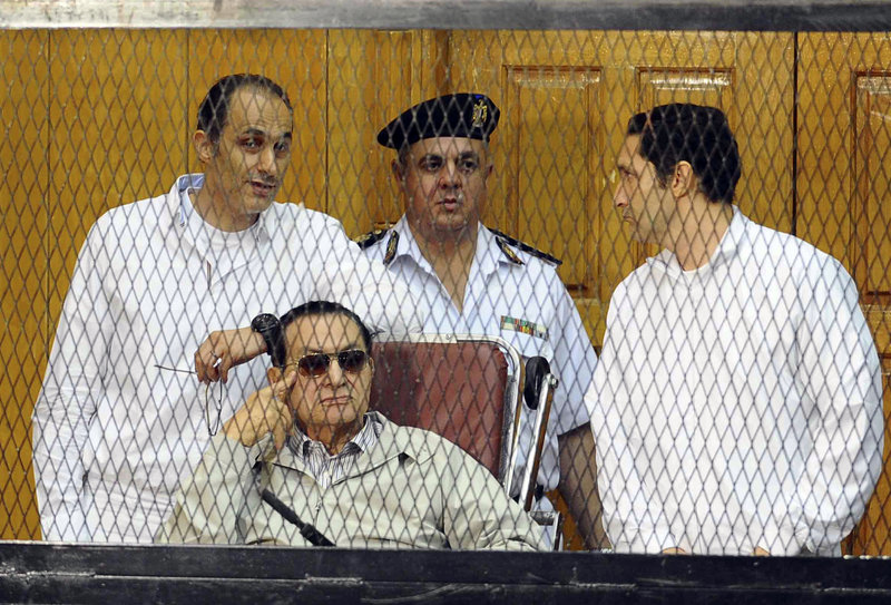 Former Egyptian President Hosni Mubarak, seated, and his sons Gamal Mubarak, left, and Alaa Mubarak, right, attend a hearing Saturday in Cairo, Egypt. The ousted autocrat was in court for the resumption of his retrial on charges related to the killings of 900 protesters in 2011.