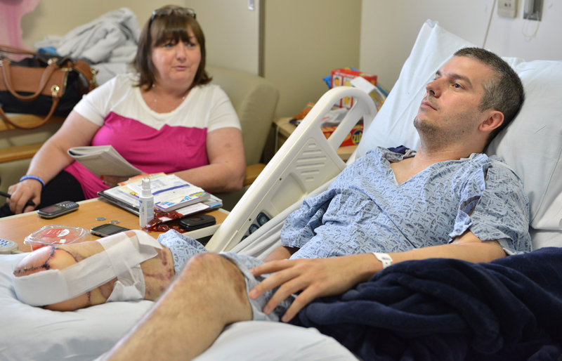 J.P. Norden of Stoneham, Mass., watches TV in the hospital with his mother, Liz Norden. He received $1.2 million from the One Fund after losing much of his right leg in the Boston Marathon attack, but his bills will exceed that.