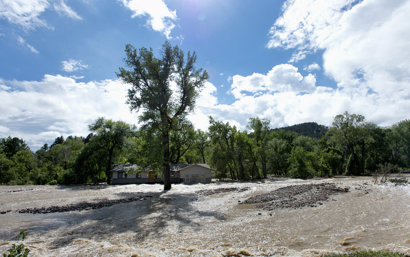 A home with floodwaters from Left Hand Creek running on both sides is seen in Boulder, Colo., on Monday. Colorado flooding was triggered by a week of torrential downpours.