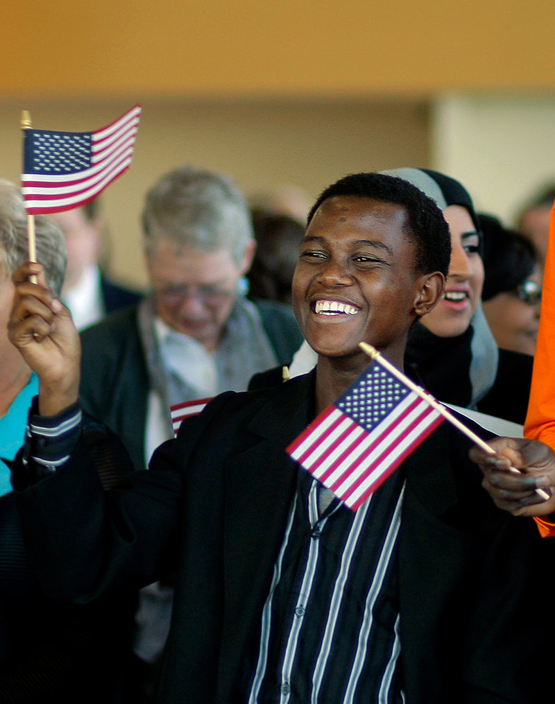 Mohamed Ali, 19, of Lewiston, originally of Kenya, waves his American flag in celebration after becoming a U.S. Citizen at a Naturalization Ceremony held at Ocean Gateway in Portland on Tuesday, September 17, 2013.