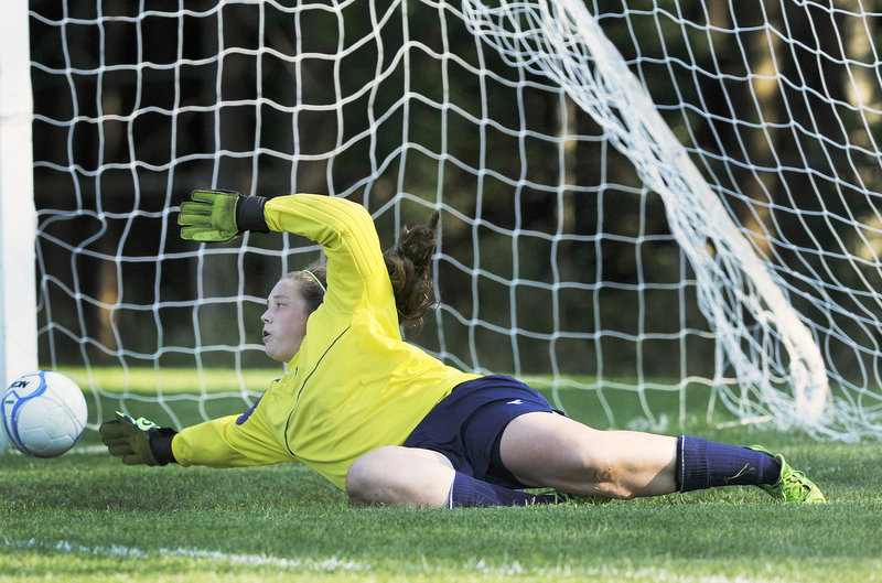 Jordyn Carr of McAuley makes a diving effort Tuesday but couldn't quite stop a shot by Shaina Speight of Biddeford – the first goal in the Tigers' 4-1 victory at Portland.