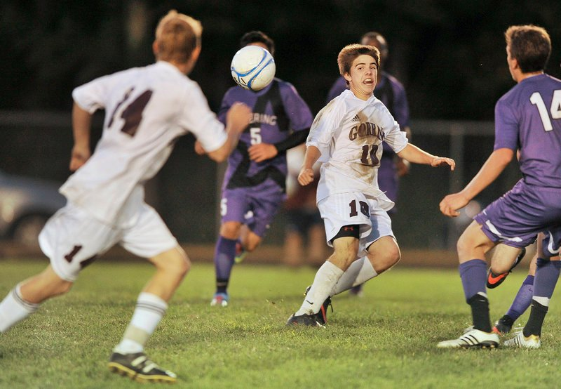 Cody Elliott of Gorham, right, passes off to Erik Andreasen as the Rams attempt to press Deering during their SMAA schoolboy soccer game Tuesday night. Deering scored in the first minute and held on for a 1-0 victory.
