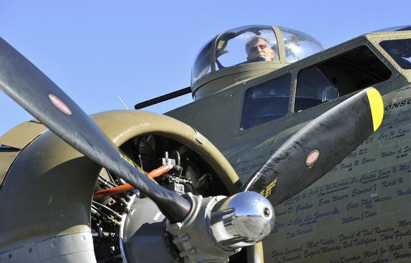 John Caylor, 73, of Dayton, an aficionado of vintage warplanes, looks out one of the gun turrets of a B-17 bomber, one of three World War II aircraft on display Wednesday at the Portland Jetport.