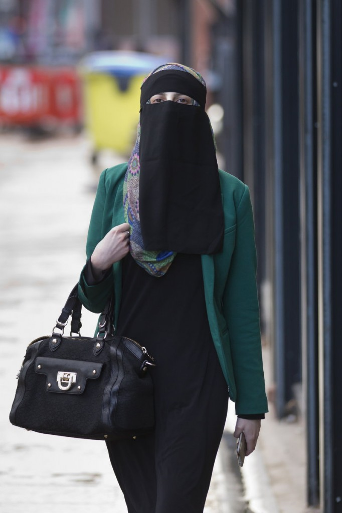 A woman walks Wednesday in Blackburn, England. A judge ruled that a Muslim woman may stand trial wearing a face-covering veil – but must remove it when giving evidence.