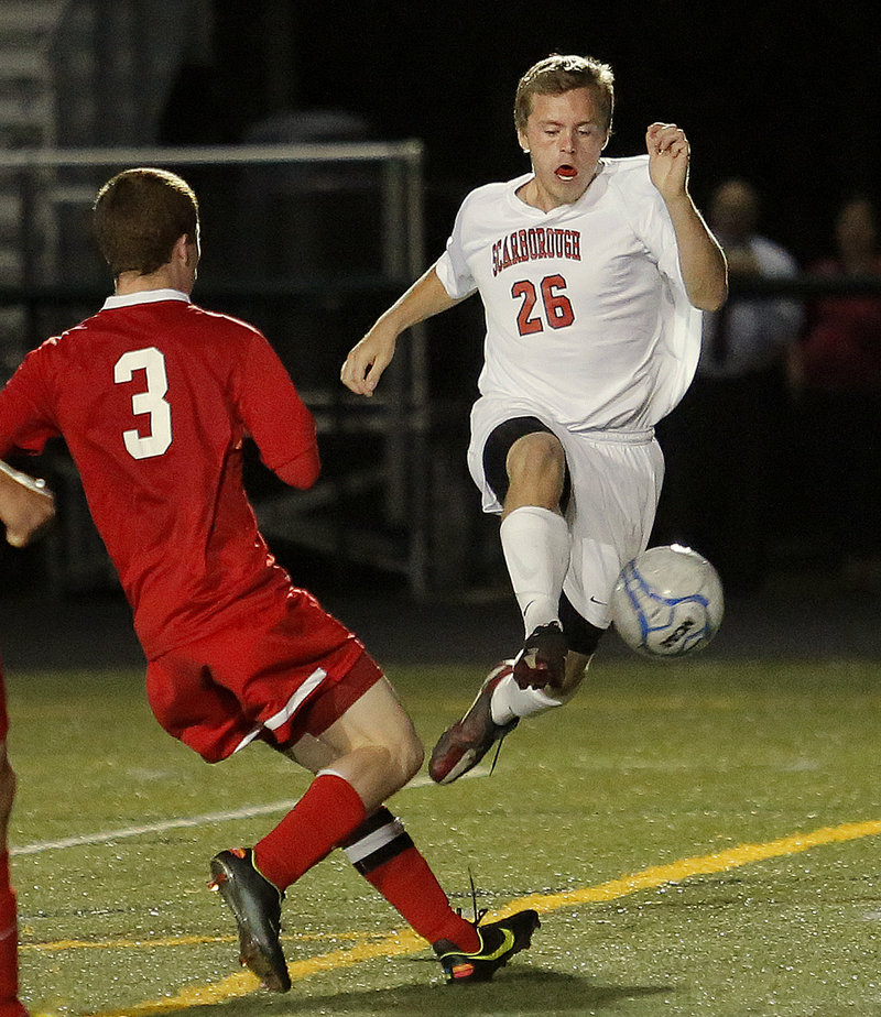 Scarborough's Austin Doody goes airborne in an attempt to retain the ball as Sanford's Evyn Nolette defends during the Red Storm's 4-0 win Thursday.