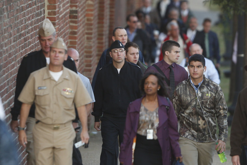 Military personnel and other workers walk along the perimeter of the Washington Navy Yard on Thursday, three days after it was the scene of a mass shooting.