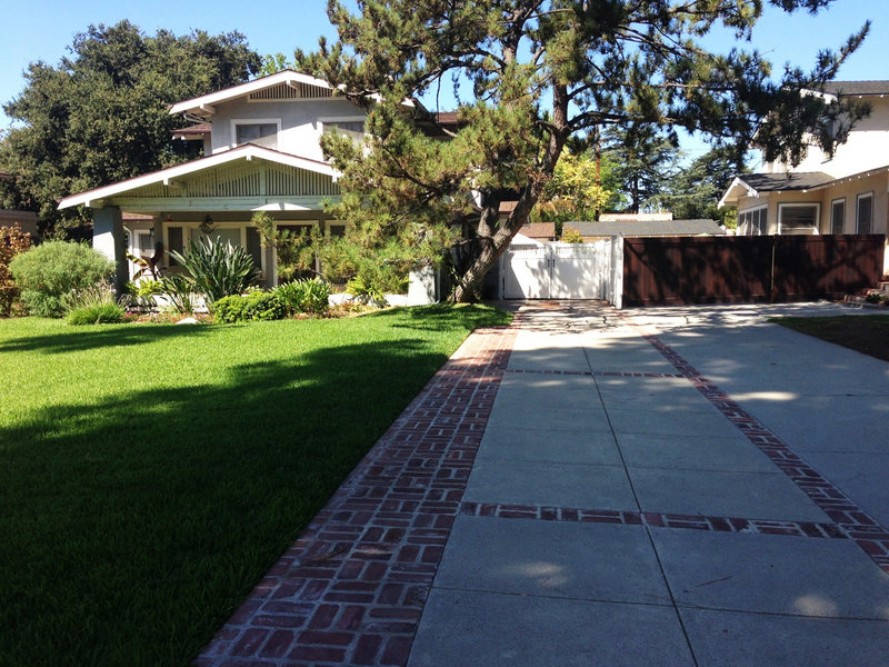 Reclaimed bricks from the 1920s accent a new concrete drive with an antique finish in Pasadena, Calif.