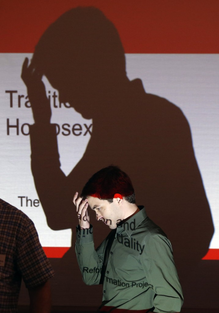 Matthew Vines walks past a projector at a conference in Prairie Village, Kan. Vines has gathered about 50 Christians to delve into his belief that the Scriptures do not condemn homosexuality.