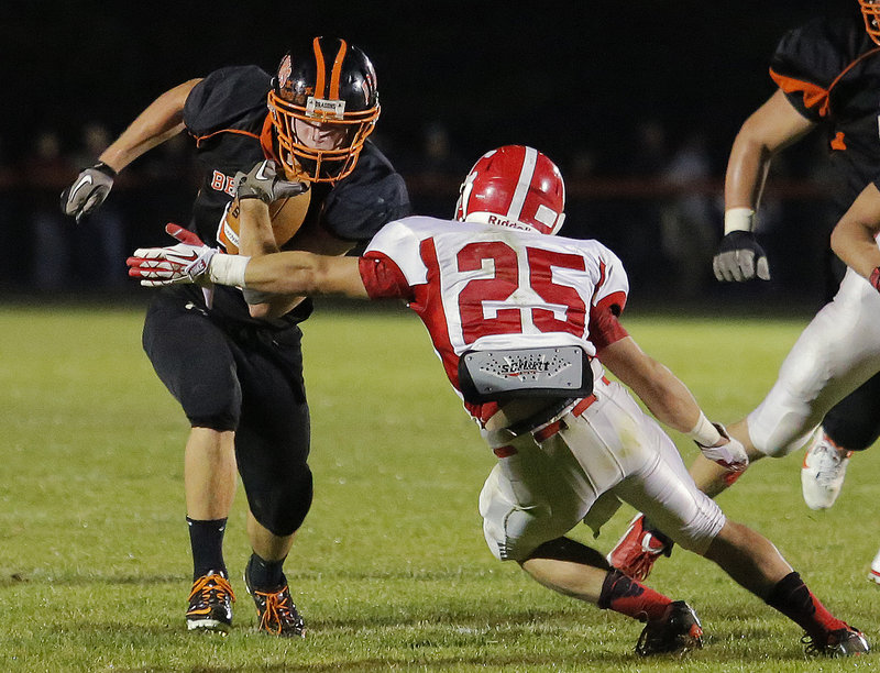 Brunswick's Lucas McCue drops his shoulder and gets ready for contact from Cony's Tayler Carrier during Friday night's game in Brunswick. The Dragons amassed 576 yards, yet still needed to put together a late drive to hold off the Rams and remain unbeaten.