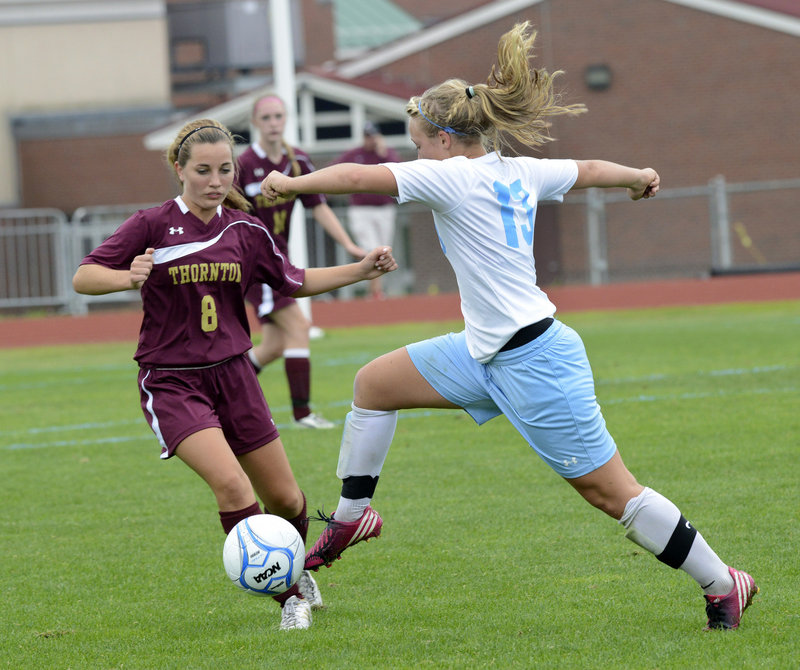 Cassie Symonds of Windham pushes the ball past Thornton Academy's Megan Hurrell during their SMAA girls' soccer match Saturday. Windham improved to 5-0 with a 1-0 triumph.