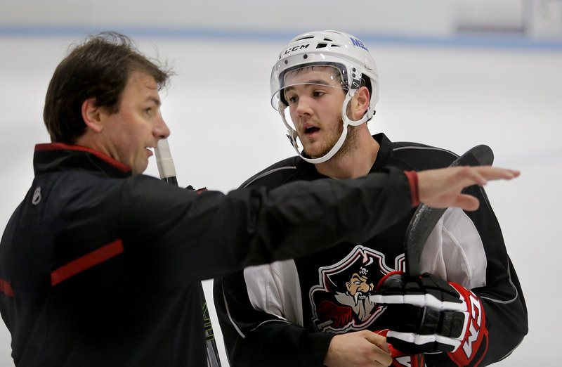 Josh Currie, shown getting his orders from assistant coach John Slaney, is one of many prospects who will be at arm's length until he proves himself AHL ready.