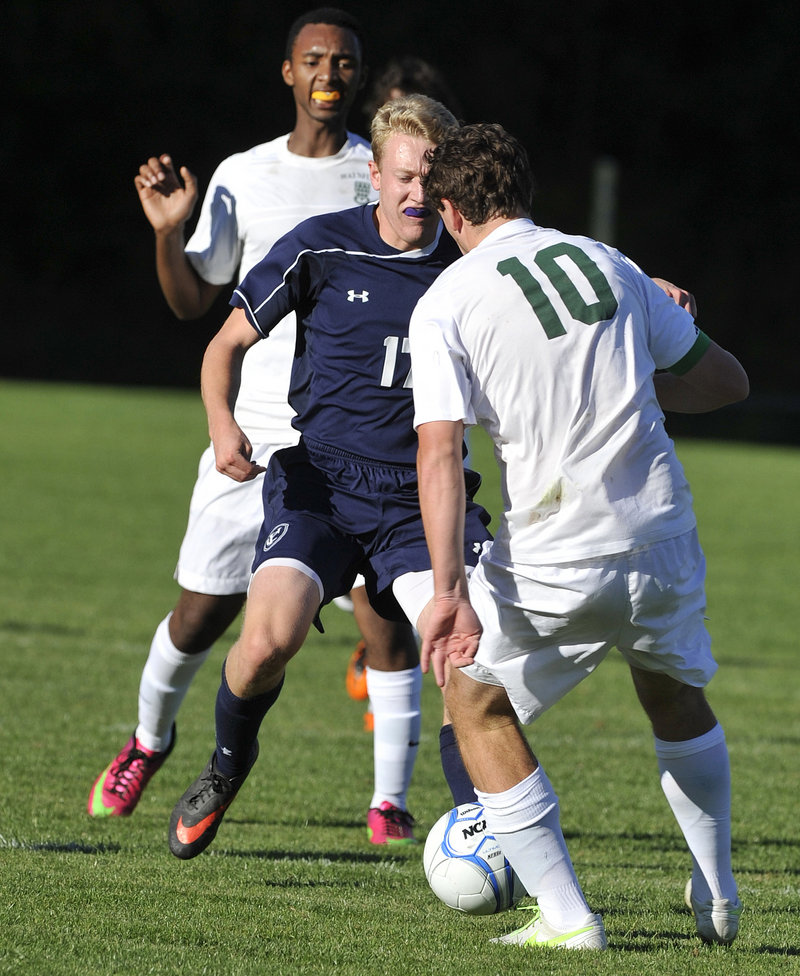 Travis Hamre of Yarmouth looks for room to dribble Tuesday while sandwiched between Henry Cleaves, foreground, and Elyse Bayizere of Waynflete during unbeaten Yarmouth's 3-0 victory.
