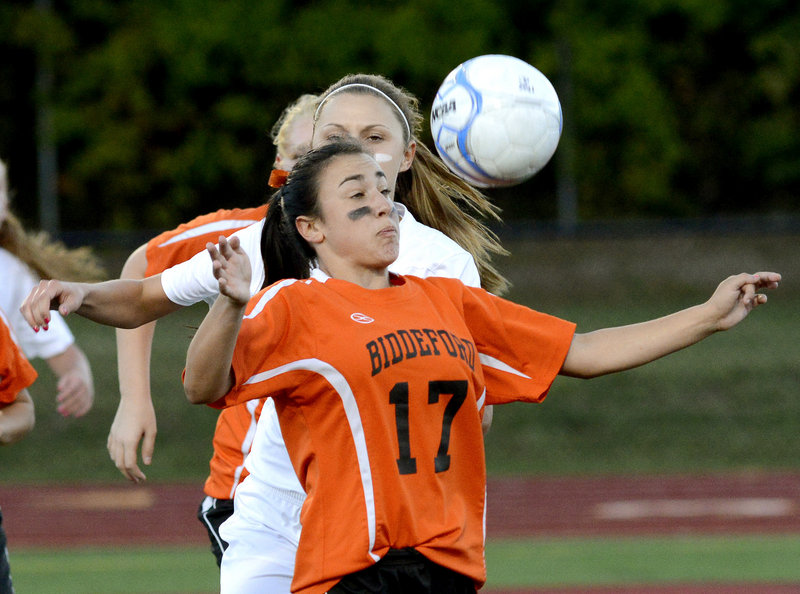 Peyton Janelle of Biddeford keeps her hands away from the ball and prepares to send it forward while taking control in front of Amanda Arnold of Thornton Academy.