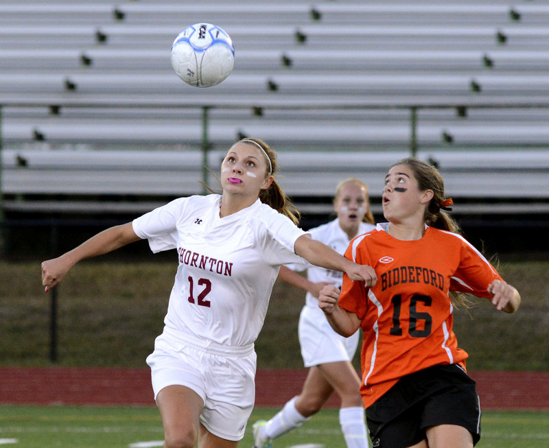 Amanda Arnold of Thornton Academy sets up for a header Wednesday night while holding off Maddy Cantara of Biddeford during their schoolgirl soccer game. Arnold had two assists and a goal in a 3-1 victory for the Golden Trojans.