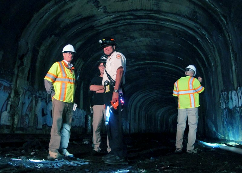 Rhode Island Gov. Lincoln Chafee, left, joins inspectors checking the condition of an abandoned railway tunnel Thursday, Sept. 26, 2013 in Providence, R.I. Chafee said he wanted to get a first-hand look at the condition of the mile-long tunnel, which was sealed off 20 years ago.