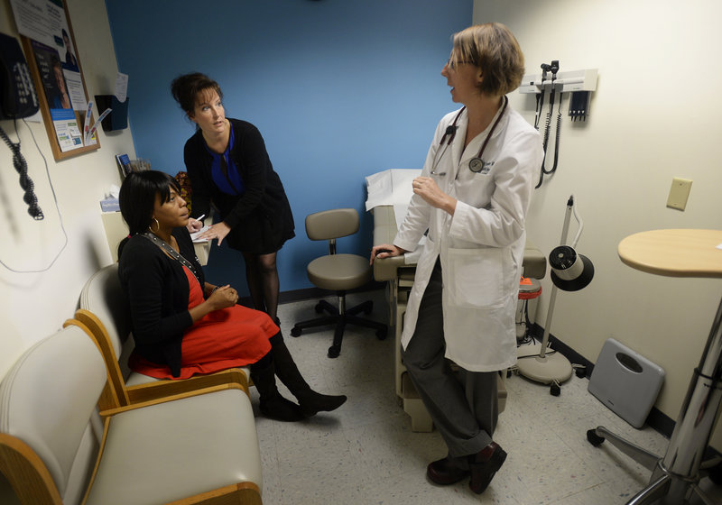 Dr. Elizabeth Frutiger, right, talks with Mireille Kabongo, left, of Portland and caseworker Michelle Bartlett of Westbrook during a visit to the Portland Community Heath Center.