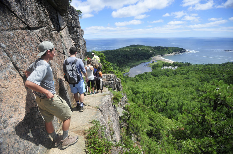 A line of hikers files up the Beehive Trail near Sand Beach at Acadia National Park in Bar Harbor. At the time this photograph was taken in July of 2014, The park was considering that it might have to close at the height of the fall foliage season if congress couldn't reach a deal on federal spending.
